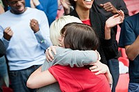 Female friends hugging at football match