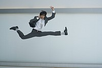 A businessman leaping in the air using mobile phone