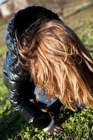 Young girl looking at the ground head down showing beautiful hair