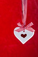 Scented ceramic heart with red and white ribbon on red background