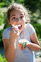 Happy young girl eating ice-cream from a cup