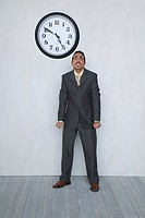 Businessman with clinched fist next to big clock on wall with the time 10 to 5.