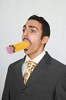 Businessman with a mouthful of pencils in his mouth.