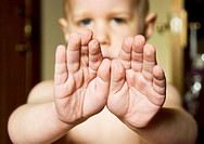 A child shows his hands after swimming - the skin of his fingers and palms is all wrinkled from being in the water for a while