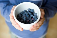 A boy holds a small white bowl containing freshly picked blueberries