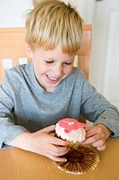 A young blond haired boy smiles as he unwraps and prepares to eat a cupcake with a pink pig on it