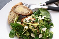 A white plate with a healthy salad and whole grain buttered bread and black and silver cutlery