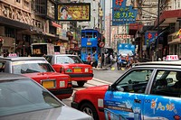 Traffic and crowds fill a busy city street in Hong Kong.