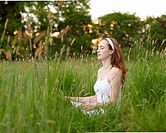 Woman meditating in meadow.