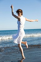 Young woman jumping on beach, laughing