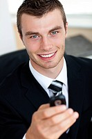 Young businessman holding mobile phone in office