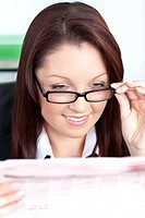 Bright businesswoman reading a newspaper wearing glasses sitting in her office