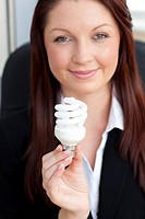 Charismatic businesswoman holding a light bulb in her office