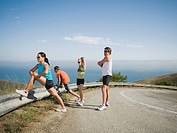 Runners stretching on the side of the road