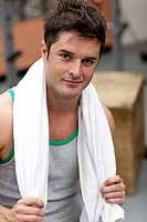 Handsome athletic man standing with a towel in a fitness center