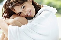 Smiling brunette woman wearing a bathrobe