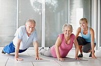 Senior couple exercising with a fitness instructor