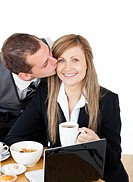 Young businessman kissing his delighted girlfriend having breakfast