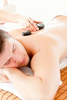 Relaxed young man receiving a back massage with hot stone in a spa center