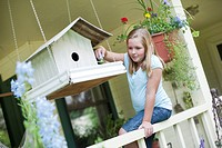 Young girl putting seeds in birdhouse