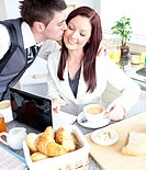 Attractive businessman kissing his bright girlfriend while having breakfast in the kitchen