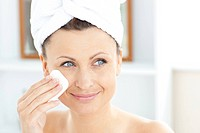 Young woman putting cream on her face wearing a towel in the bathroom at home