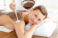 Pretty young woman enjoying a beauty treatment with mud in a health spa
