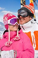 Smiling skiers in caps and goggles hugging