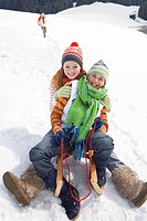 Brother and sister riding sled together in snow