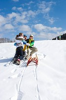 Laughing family with sled hugging on ski slope