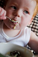 A baby feeding himself in a high chair, using a spoon