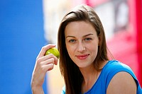 Young lady eating a healthy snack of an apple in the Custard Factory, Birmingham