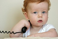 A baby holding and talking on a telephone