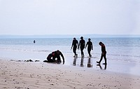 People in wetsuits on Newgale beach in West Wales