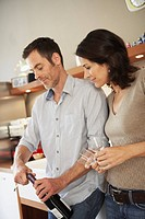 Couple opening up bottle of wine