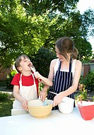 Sisters preparing cakes outdoors