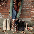 Young woman putting Wellington boots on outside in the garden