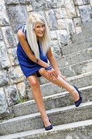 Touching leg on the staircase young woman in a Blue dress