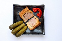 Two wedges of common British pork pie with miniature gherkins and roasted red peppers