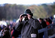 Man at horse race watches the racing through binoculas