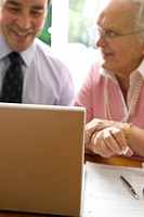 Portrait of a businessman and woman sitting in front of laptop smiling