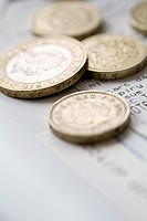 Close up of loose pound sterling coins on top of receipts