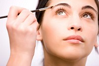 Close up of a young woman applying make up on her eyebrow with a brush