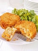 Vegetable cakes coated in breadcrumbs with a green salad