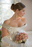 Bride in a white wedding gown holding a bouquet of roses