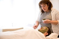 Beautician applying green facial mask on woman face with brush