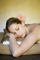 Young woman resting on a gold pillow with her eyes closed
