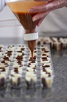 Close up of a chef's hands filling chocolate candy moulds