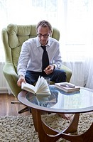 Businessman Putting Book on Coffee Table