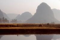 Farm workers thresh rice amid karst peaks.